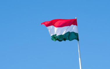 Hungarian flag waving against blue sky