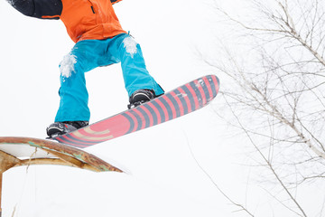 Picture of bottom of sportive man skiing on snowboard with springboard