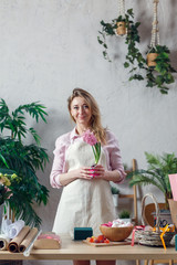 Photo of florist blonde in apron at room with flowers