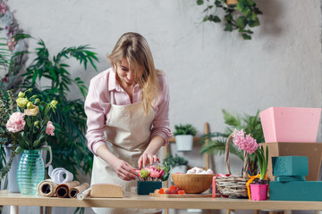 Image of blonde florist making composition of flowers