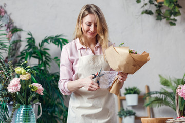 Photo of florist woman in apron with bouquet of kraft paper on background of indoor plants