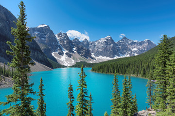Beautiful turquoise waters of the Moraine Lake with snow-covered peaks above it in Rocky Mountains, Banff National Park, Canada.