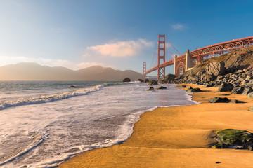 Golden Gate Bridge at sunset seen from the  beach in San Francisco, California.