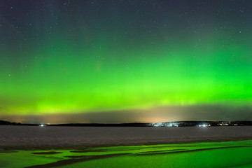 Night sky view of beautiful green aurora borealis (northern polar lights) in Finland with reflection on the frozen and snowy lake during geomagnetic storm