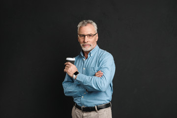Portrait of adult man 60s with grey hair and beard posing on camera with holding takeaway coffee from paper cup, isolated over black background