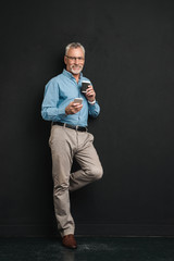 Photo of mature man 60s with grey hair and beard using сell phone while drinking takeaway coffee from paper cup, isolated over black background