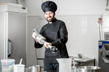 Funny portrait of a chef cook standing with blender in the professional kitchen during the process of ice cream making