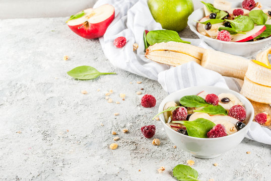 Healthy summer breakfast, fruit and berry salad with spinach, granola, apple and banana, white marble background