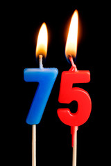 Burning candles in the form of 75 seventy five figures (numbers, dates) for cake isolated on black background. The concept of celebrating a birthday, anniversary, important date, holiday