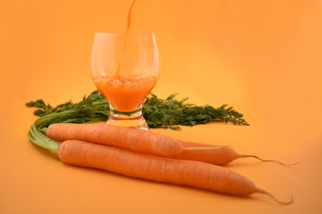 Pouring carrot juice stock images. Glass of carrot juice with carrots. Carrot on orange background