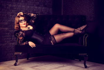 Beautiful young woman posing in stockings and Venetian mask on sofa.  Retro glamor vintage woman. Carnival  Masquerade sexy women