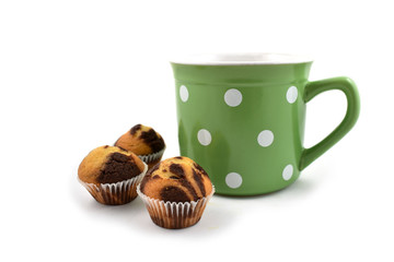 Muffin with a mug stock images. Green mug with dots. Muffins and green mug. Muffins with cup on a white background. Big spotted mug. Sweet snack still life
