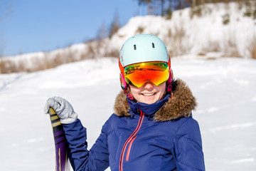Portrait of sporty woman wearing helmet with snowboard looking at camera