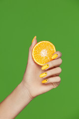 Nails Design. Hands With Fashion Manicure Holding Orange