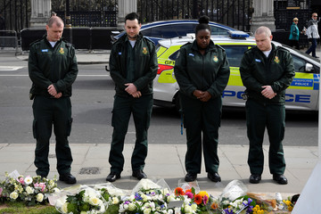 Emergency services workers lay flowers and pay their respects at Parliament Square in Westminster on the anniversary of the Westminster Bridge attack in London