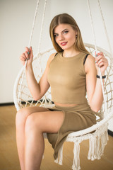 Beautiful girl in a white hanging chair on a white background.
