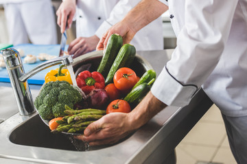cropped image of chef washing vegetables at restaurant kitchen