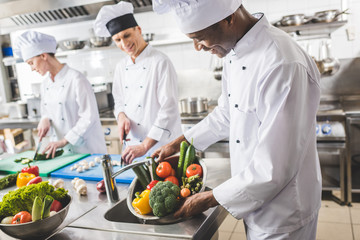 smiling african american chef washing vegetables at restaurant kitchen