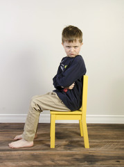 An angry little boy sits in a yellow time out chair on a wooden floor