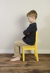 An angry little boy sits on a yellow time out chair