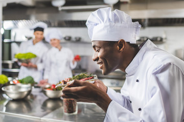 smiling african american chef sniffing raw meat with herbs at restaurant kitchen
