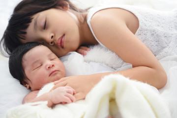Older sister and her newborn sister sleep.