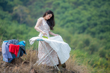 Young women ironing on cliffs in nature, working life concept Work out