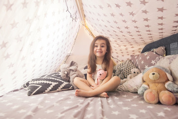 Cute happy little girl playing with toys and dreaming in teepee and bed. Close up photo of happy child