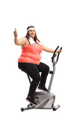 Overweight woman exercising on a stationary bike and making a thumb up gesture