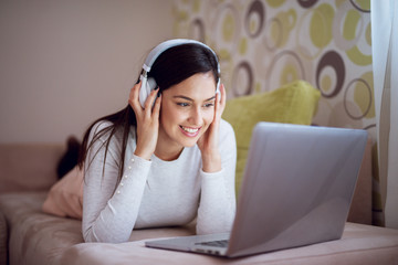 Young pretty joyful woman laying on her sofa leaned on elbows is smiling while she is enjoying music from a laptop with headphones on.