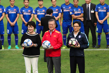 South Korea's President Moon, First Lady Kim and Vietnam's DPM Dam pose for a photo in front of the Vietnam under-23 national team in background at a stadium in Hanoi