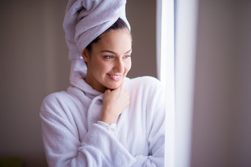 Young beautiful joyfull woman in a robe with a towel around her hair is smiling and feeling fresh after the shower while looking out of the window and feeling cozy.