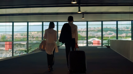 Couple in formal wear walking with bags in airport, business trip, partners