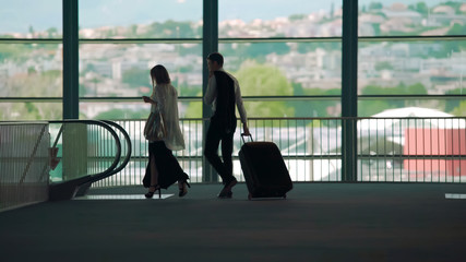 Business trip, man and woman walking to escalator in airport, carrying luggage