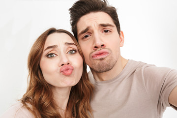 Closeup picture of amusing couple in relationship looking on camera and blowing air kiss while photographing themselves, isolated over white background