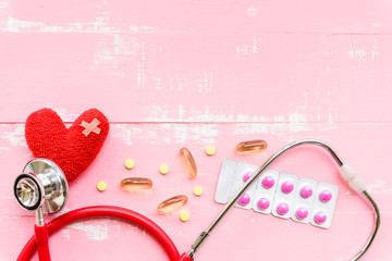 World health day, Healthcare and medical concept. Red heart with Stethoscope and yellow Pill on Pastel white and pink wooden table background texture.