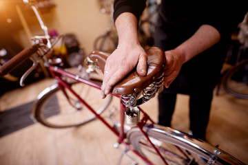 Close up view of man's hands pressing bicycle seat to check its suspension.