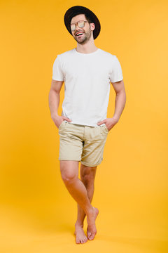 young barefoot man in shorts and sunglasses standing with hands in pockets and laughing isolated on yellow