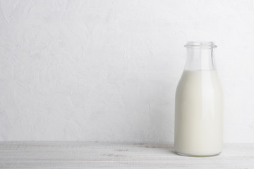 Full glass bottle of milk on white wooden table background with copy space