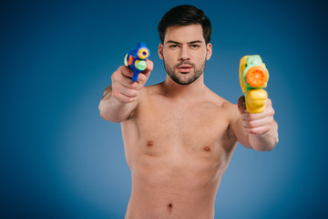 handsome bearded young man holding water guns and looking at camera on blue