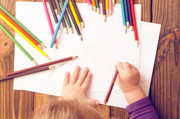 The child's hands are painted with colored pencils on a white sheet of paper on a wooden table