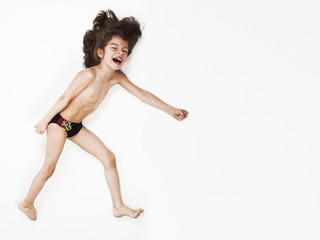 Young Caucasian boy running action on light background