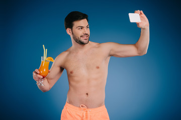 handsome shirtless young man in shorts holding glass of summer cocktail and taking selfie with smartphone on blue