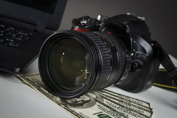 A lot of dollars near the camera and laptop