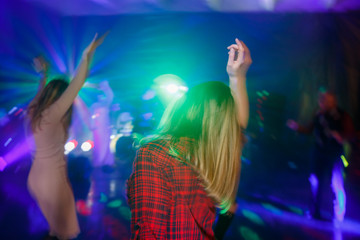 The girl is dancing with her back on the dance floor. Multicolored disco lights