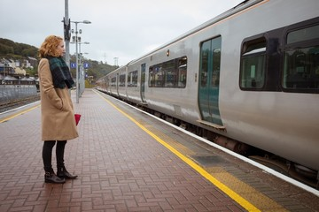 Beautiful young woman standing on platform in front of train