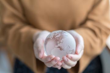 世界地図の彫られた水晶を持つ女性