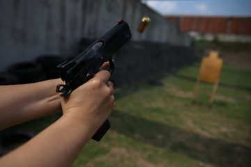 A woman shoots at target during a practice session at a shooting range in Bangkok