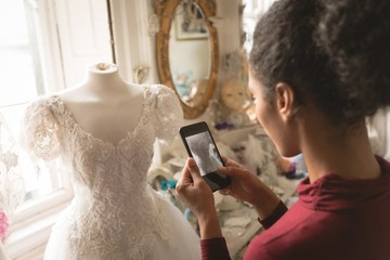 Woman taking photo of wedding dress mobile phone in the boutique