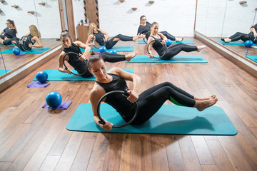 Attractive girls in sportswear training with pilates rings during exercise class in health club